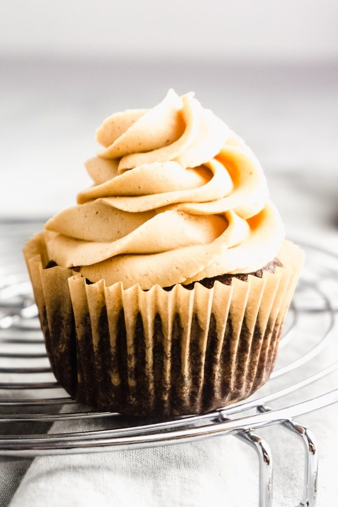 one chocolate keto cupcake with peanut butter buttercream on a cooling rack