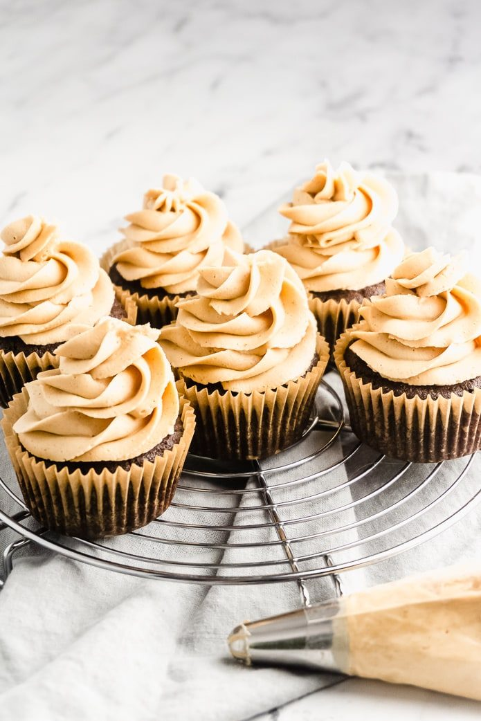 low-carb chocolate cupcakes with peanut butter icing and a frosting piping bag