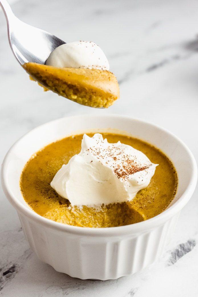 spoon of keto pumpkin custard with whipped cream