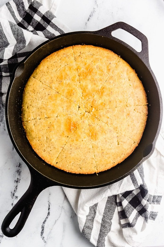 baked keto cornbread cut into wedges in a cast iron pan