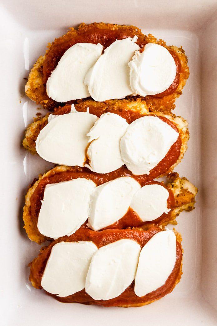 fresh mozzarella cheese slices on top of keto chicken breast