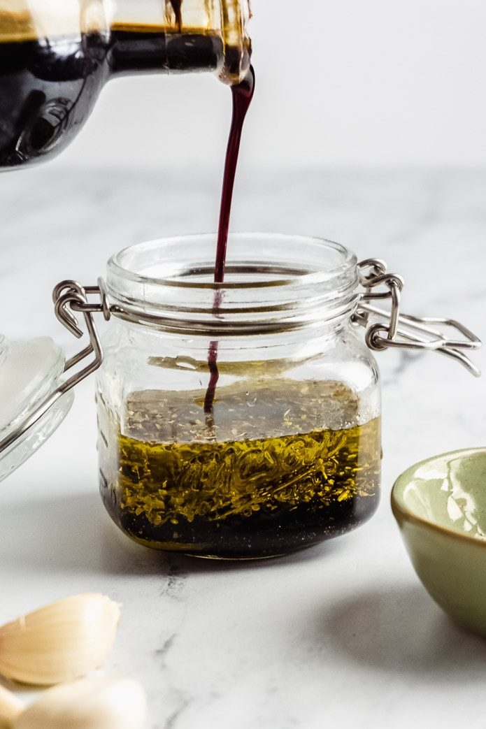 pouring vinegar into a mason jar to make salad dressing