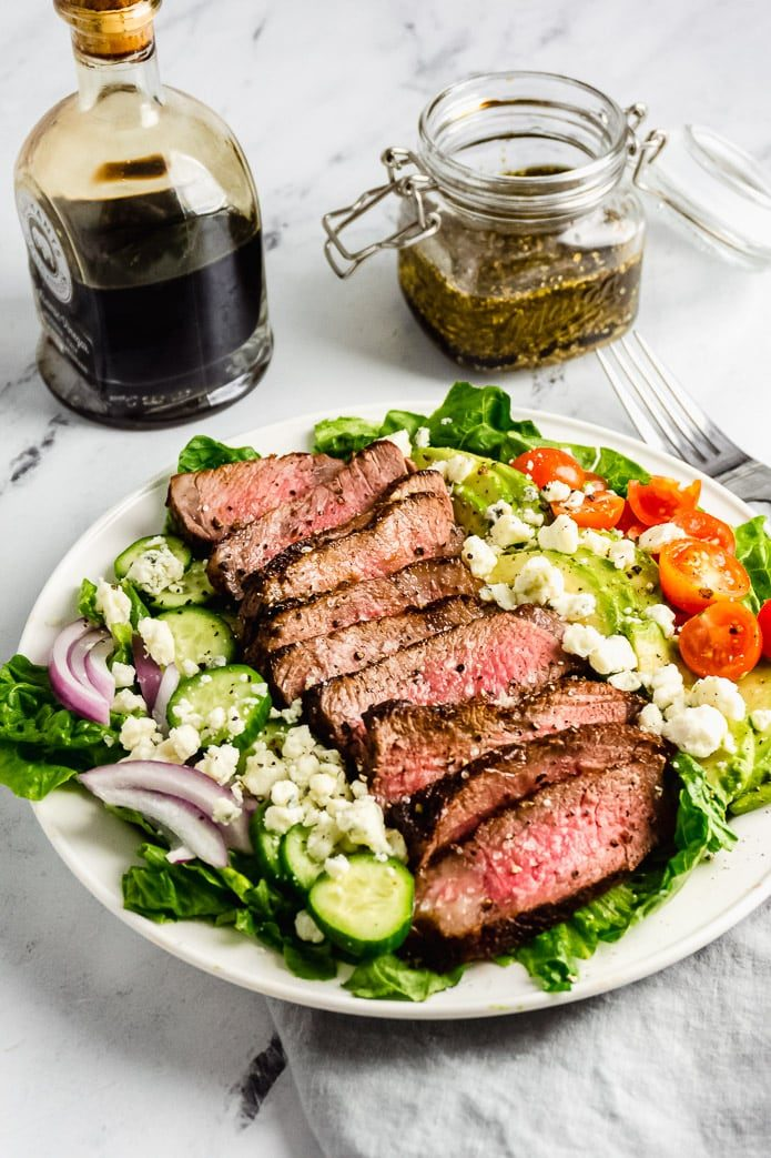 grilled steak salad with keto balsamic vinegar in a white plate