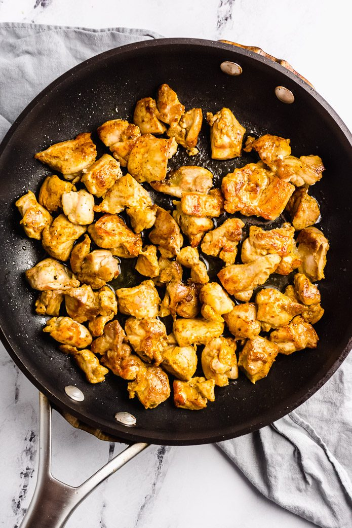 browned chicken pieces in a black skillet